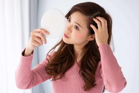 髪の毛を確認する女性
